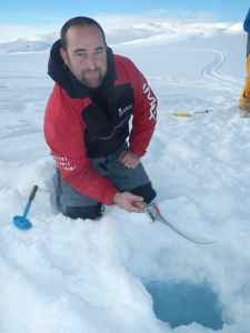 Sam fishing for char. Not the scoop, essential for clearing rapidly forming slush out of your hole!